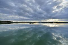 Clouds and crepuscular sunrays refelcted in lake at sunrise, Woerthsee Lake, - stock photo
