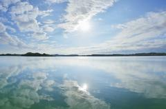 Blue sky, clouds and sun reflected in lake, Lake Woerthsee, Bavaria, Germany Stock Photos