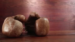 Vintage boxing gloves on wooden table. Stock Footage