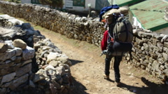 Himalayas Nepal porter carrying load down trail near village in SoluKhumbu, - stock footage