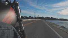 Low side shot of riding motorcycle next to ocean Stock Footage