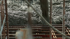Worker pulling large hose for concreting of steel reinforced concrete. Low angle Stock Footage