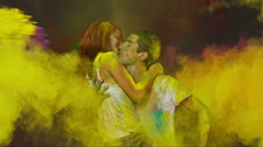 Holi colorful hits. Beautiful Young Couple in Love kiss and hug . Slow Motion. Stock Footage