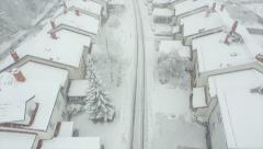 AERIAL: Flying above suburbia in heavy snow - stock footage