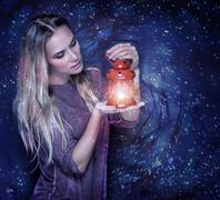 Portrait of beautiful woman with glowing lantern in hands over starry sky - stock photo