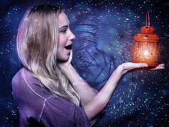 Closeup portrait of cute blond girl with surprise looking on red glowing lantern Stock Photos