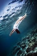 Active woman diving to the sea bottom - stock photo