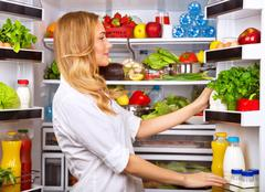 Happy female search something in the fridge - stock photo