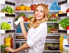 Stock Photo of Woman chosen milk in opened refrigerator