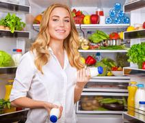 Woman chosen yogurt in opened refrigerator - stock photo