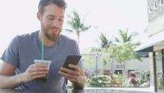 Man on cafe using smart phone app text messaging sms drinking iced coffee Stock Footage
