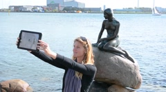 Copenhagen Denmark Little Mermaid monument Den Lille Havfrue with tourist woman Stock Footage