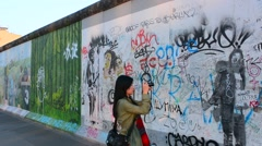 Berlin Germany remaining part of Berlin Wall with Chinese tourist with artists - stock footage