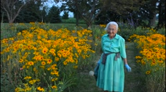 Plain City Ohio 89 year old Amish Great Grandmother watering her flowers in Stock Footage