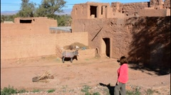 Morocco Sekoura small village Berber homes and woman tourist taking photos Stock Footage