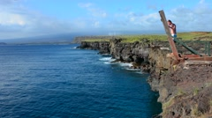South Point Hawaii Big Island cliff pole young man diving into water danger Stock Footage