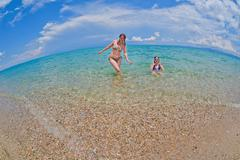 Mother and daughter bathe in the sea - stock photo