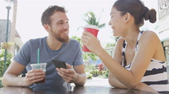 Cafe couple looking at smart phone screen app laughing having fun on date Stock Footage