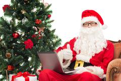 Man in costume of santa claus with laptop Kuvituskuvat