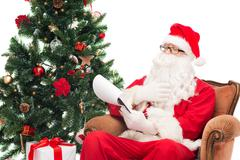 Man in costume of santa claus with notepad Kuvituskuvat