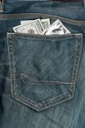 US dollars and condom in the jeans pocket - stock photo