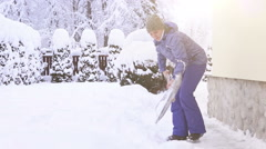Young woman shoveling snow near the house after intense snowfall Stock Footage