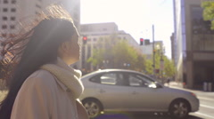 Mixed Race Young Woman Walks In Big City On A Windy Day (Lens Flare) Stock Footage