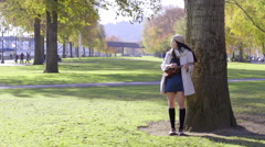 Mixed Race Young Woman Plays Her Ukulele In A City Park In Autumn Stock Footage