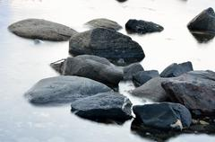 Beautiful stones in misty arctic circle fjord water - stock photo