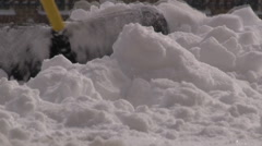Ground level view of snow shovel clearing a pile of snow. Stock Footage