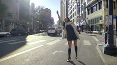 Mixed Race Young Woman Tries To Hail A Cab In The City On A Beautiful, Windy Day - stock footage