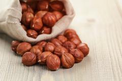 Sack bag full of hazelnut kernels, rustic style photo Stock Photos