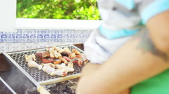 Man with a baby at Brazilian family BBQ Stock Footage