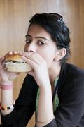Young teenager eating junk food. Stock Photos