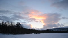 Colourful sky over snowy mountain peak in winter as the first sunshine appears Stock Footage