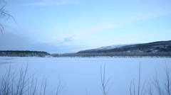 Snowy winter landscape with moving clouds and majestic mountain over riverbed Stock Footage