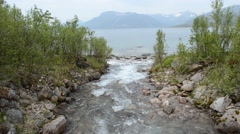 Beautiful river flowing into cold fjord ocean water with mountain range in back Stock Footage