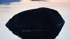 Beautiful big black stone in fjord water with small ripples Stock Footage
