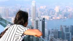 Woman watching sunset over Victoria Harbor from Victoria Peak Stock Footage