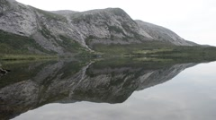 Beautiful silent and reflective mountain lake and mountain in summer senja Stock Footage
