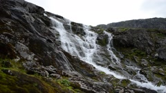Fast flowing mountain waterfall down slippery mountain side Stock Footage