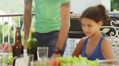 Family enjoying food and drink at a Brazilian family BBQ - stock footage