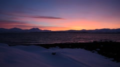 Red orange sunset behind snowy mountain range and cold fjord water Stock Footage