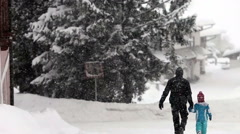 Father and son, walking in the snowy day in a village Stock Footage