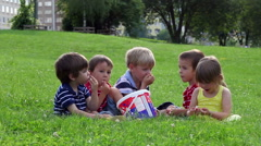 Group of adorable kids, eating popcorn in the park, laughing Arkistovideo