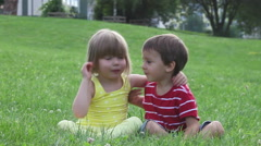 Two kids on a lawn, having fun, smiling and kissing Stock Footage