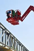 red hydraulic construction cradle against the blue sky - stock photo