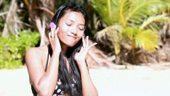Girl in swimsuit with headphones singing on the beach Stock Footage