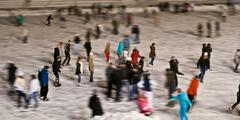 Winter skating rink in the evening with moving people Stock Photos
