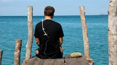 A man sits on a pier with a noose around his neck Stock Footage
